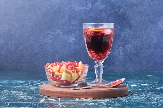 Ensalada de frutas con una copa de vino en azul.