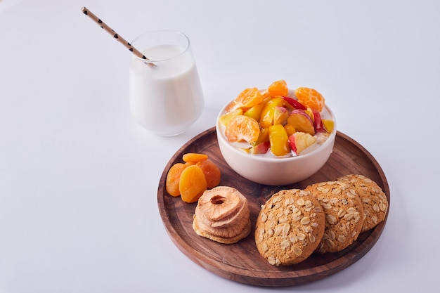 Ensalada de frutas en crema con galletas de avena en una placa de madera con un vaso de leche a un lado, vista superior.