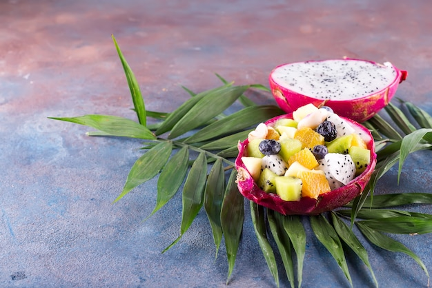 Ensalada de frutas exóticas servida en la mitad de una fruta de dragón en hojas de palma en el fondo de piedra, espacio de copia