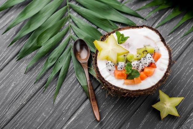 Ensalada de frutas en placa de coco alta vista