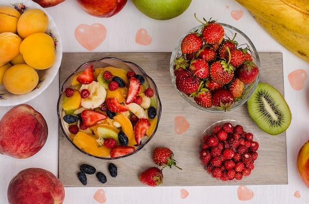 Ensalada de frutas de postre festivo con fresas y fresas y frutas con corazones sobre una superficie blanca. día de san valentín. cumpleaños. dieta de alimentos crudos