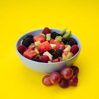 Ensalada de frutas sabrosas sobre fondo amarillo