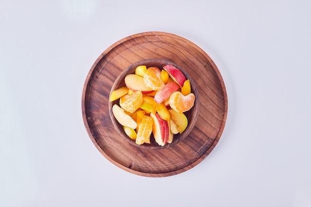 Ensalada de frutas de temporada en una taza de madera, vista superior.