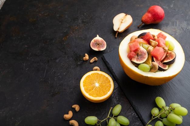 Ensalada de frutas vegetariana de sandía, uvas, higos, pera, naranja, anacardo en tablero de pizarra.