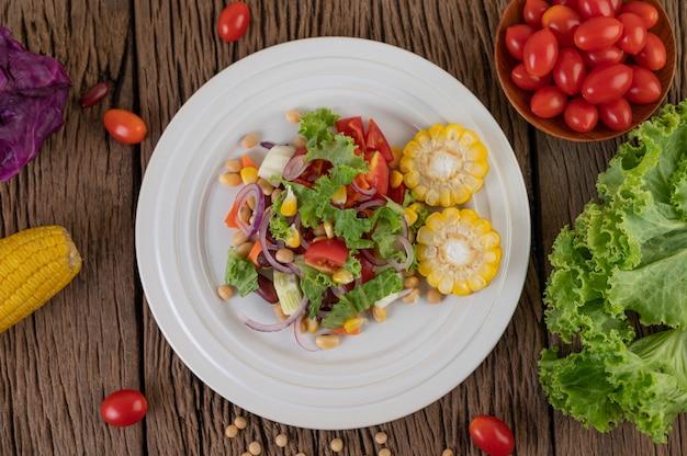 Ensalada de frutas y verduras en un plato blanco sobre un piso de madera