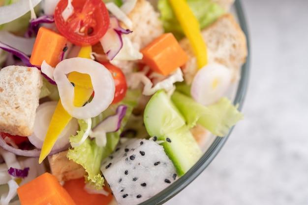 Ensalada de frutas y verduras en un plato blanco.