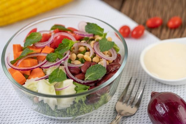 Ensalada de frutas y verduras en un vaso de vidrio sobre un fondo blanco
