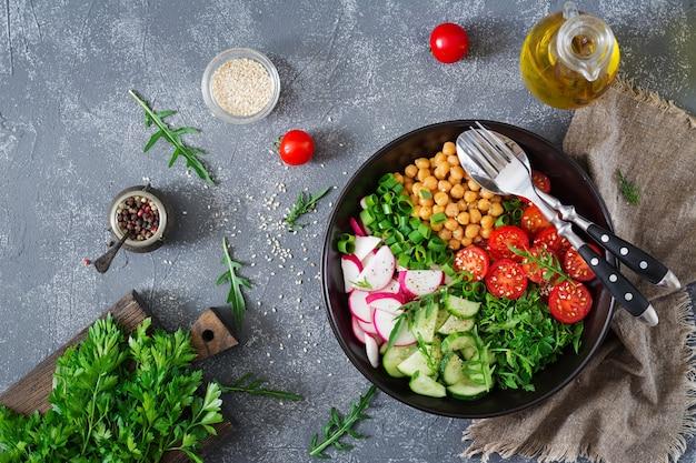 Ensalada de garbanzos, tomates, pepinos, rábanos y verduras. comida dietética ensalada vegana vista superior. endecha plana. tazón de buda