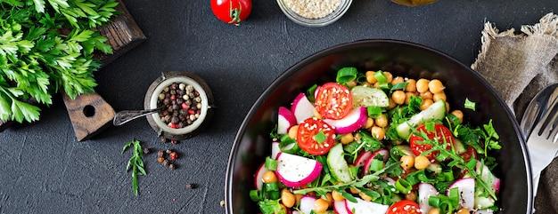 Ensalada de garbanzos, tomates, pepinos, rábanos y verduras. comida dietética ensalada vegana vista superior. lay flat