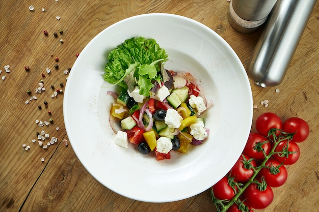 Ensalada griega clásica con tomate, cebolla, pepino, queso feta y aceitunas negras con aceite de oliva en un plato blanco sobre una superficie de madera