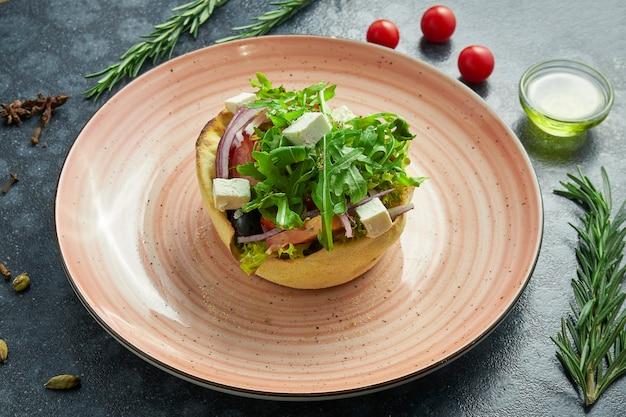 Ensalada griega clásica con tomates, cebollas, pepino, queso feta y aceitunas negras en pita en un plato rosa sobre una superficie oscura