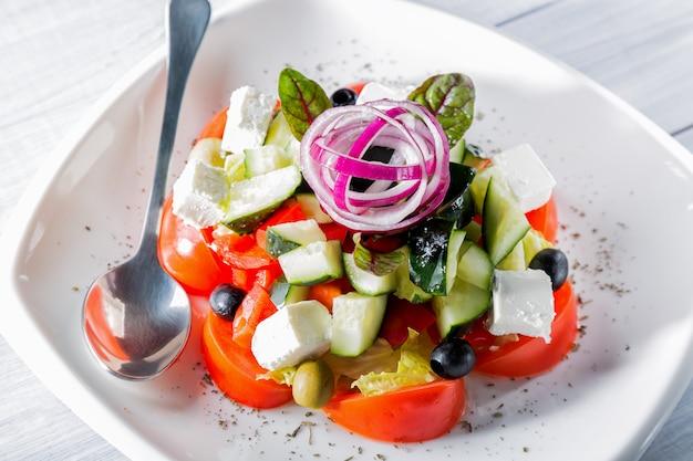 Ensalada griega fresca en plato blanco con cebolla