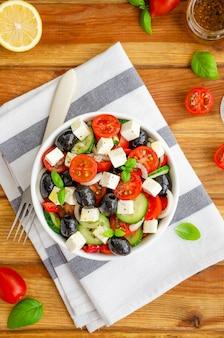 Ensalada griega de jugosas verduras frescas, queso feta, hierbas y aceitunas en un recipiente blanco sobre una madera