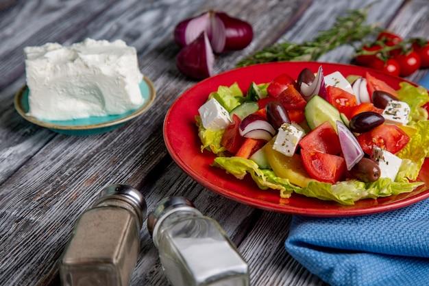 Ensalada griega de pepino fresco, tomate, pimiento dulce, lechuga, cebolla roja, queso feta y aceitunas con aceite de oliva sobre fondo de madera. comida sana