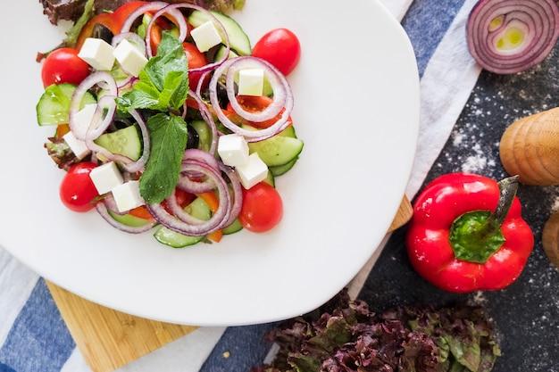Ensalada griega en una placa blanca en fondo de piedra oscuro. la comida fresca es plana.
