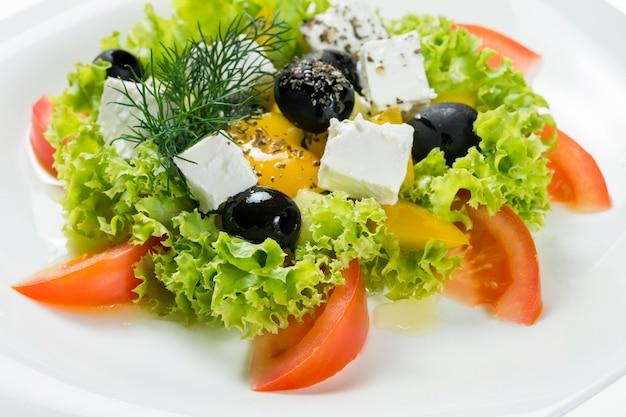 Ensalada griega en plato en blanco