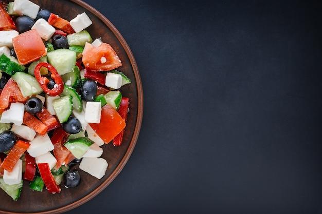 Ensalada griega en un plato sobre un fondo oscuro