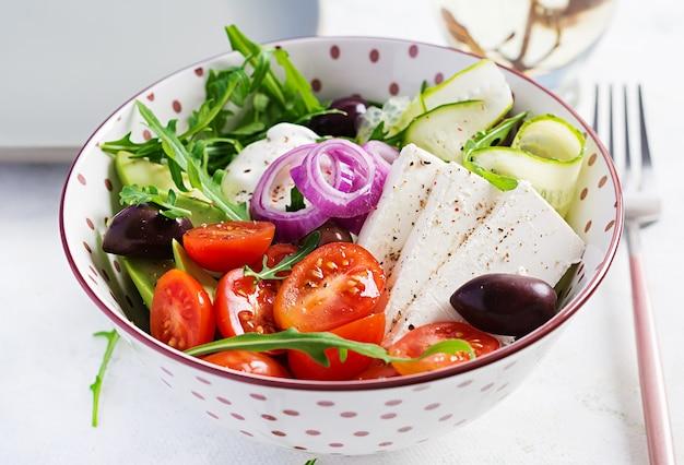 Ensalada griega saludable de pepino fresco, tomate, aguacate, rúcula, cebolla morada, queso feta y aceitunas