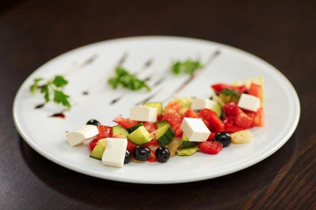 Ensalada griega con verduras, queso feta y aceitunas negras.