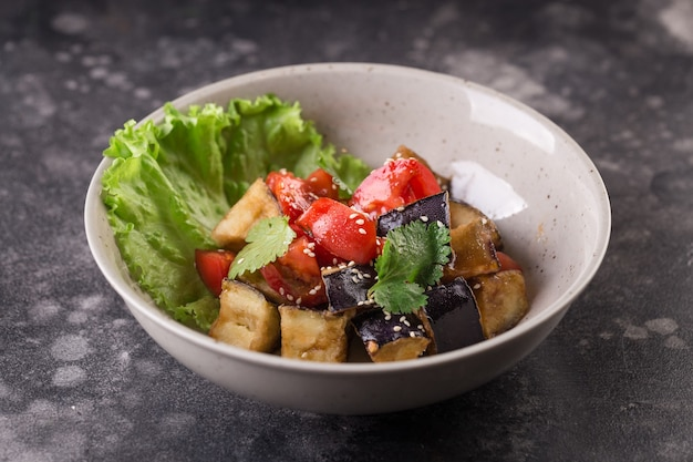 Ensalada guisada de berenjena y tomate con hoja de listón y semillas de sésamo servida en un plato blanco