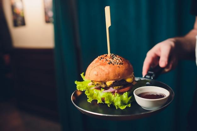 Ensalada de hamburguesa con papas fritas en las manos de los camareros.