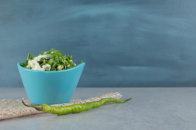 Ensalada de hierbas verdes en una taza sobre la mesa de hormigón.
