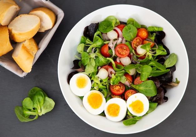 La ensalada de huevo mezclada con tomates dulces, ajo en vinagre, cebolla y espinacas son una dieta saludable para cada comida.
