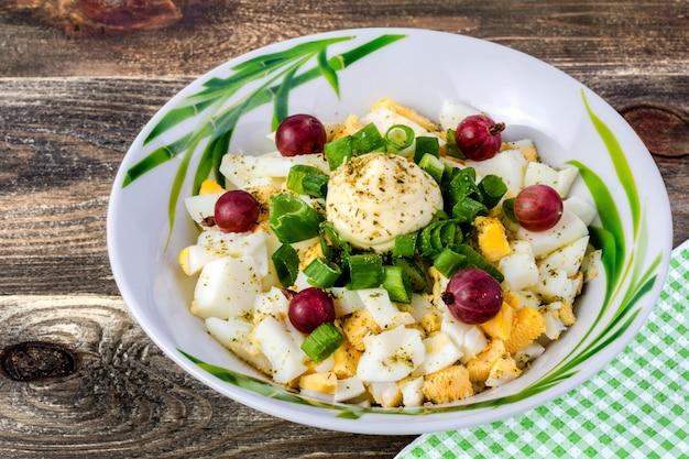 Ensalada de huevos y cebollas, grosellas decoradas, en un plato blanco sobre una mesa de madera.