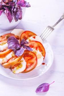 Ensalada italiana caprese con mozzarella, tomate, albahaca y pesto