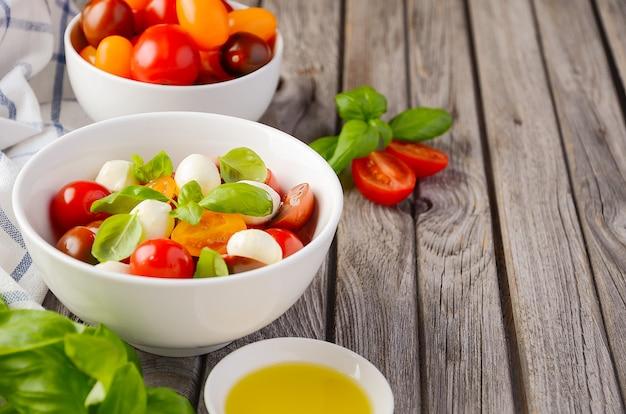 Ensalada italiana caprese con tomates cherry, mozzarella pequeña y albahaca fresca.