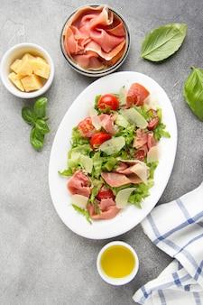 Ensalada con jamón (parma, jamón, serrano, jamón serrano), queso parmesano, lechuga, tomates cherry en un plato