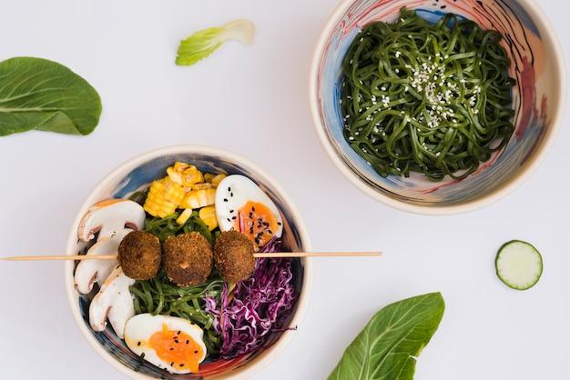 Ensalada japonesa de algas chuka con fideos sobre fondo blanco