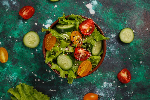 Ensalada de lechuga fresca con tomates amarillos, rodajas, tomates cherry, tazón de semillas en la oscuridad,
