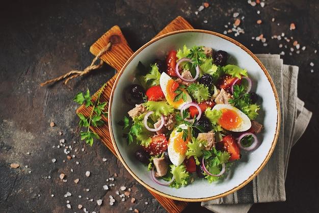 Ensalada de lechuga orgánica saludable con atún enlatado, tomates cherry, aceitunas secadas al sol, cebolla roja, huevo y parmesano