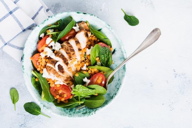 Ensalada de lentejas rojas, hojas de espinaca, tomates cherry, carne de pollo y queso mozzarella