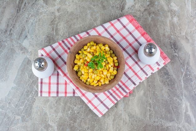 Ensalada de maíz en un recipiente junto a la sal sobre un paño de cocina sobre mármol.