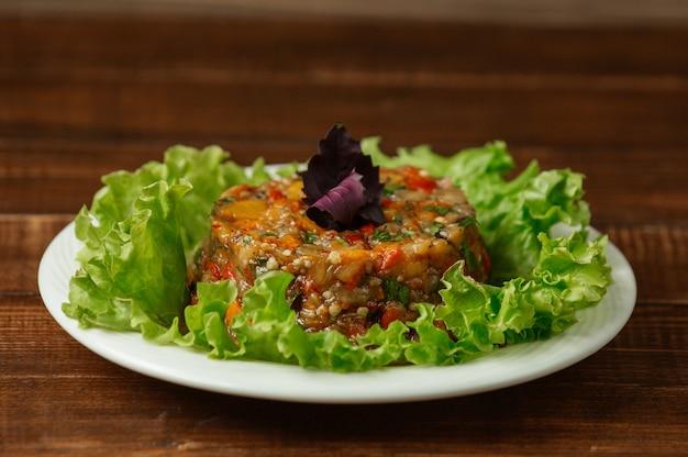 Ensalada de mangal hecha de verduras a la parrilla y servida con hojas rojas de basílica en la parte superior