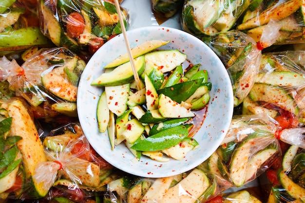 Ensalada de mango picante tailandesa en un tazón y en un envasado de plástico que se vende en el mercado matinal