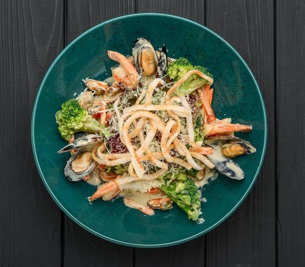 Ensalada de mariscos frescos con camarones, mejillones y verduras sobre un fondo negro
