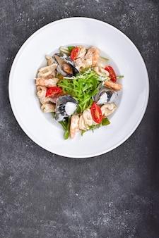 Ensalada de mariscos con mejillones, calamares, camarones, en un plato blanco redondo, en un espacio gris