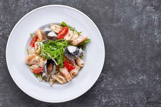 Ensalada de mariscos con mejillones, calamares, camarones, sobre un plato blanco redondo, sobre un fondo gris