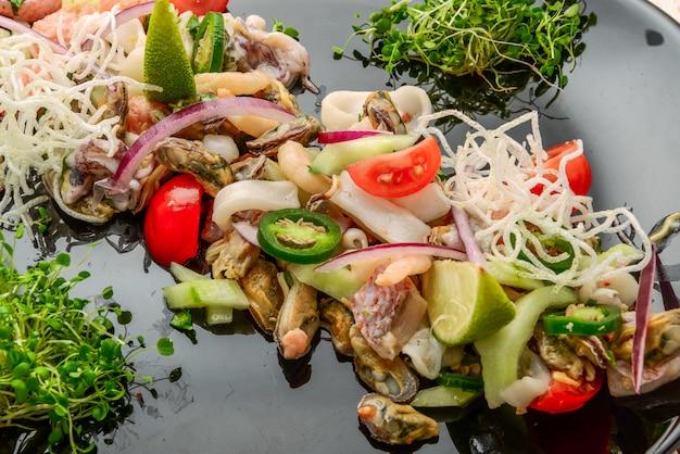 Ensalada de mariscos picante y agrio tailandés en una mesa de madera