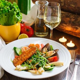 Ensalada de mariscos con salmón, camarones, mejillones, hierbas y tomates.