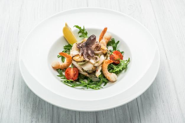 Ensalada de mariscos y vegetales con rúcula y tomates.