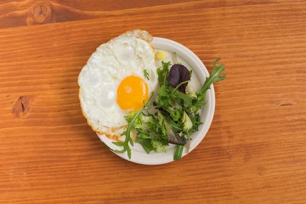 Ensalada y medio huevo frito en un plato sobre la mesa de madera