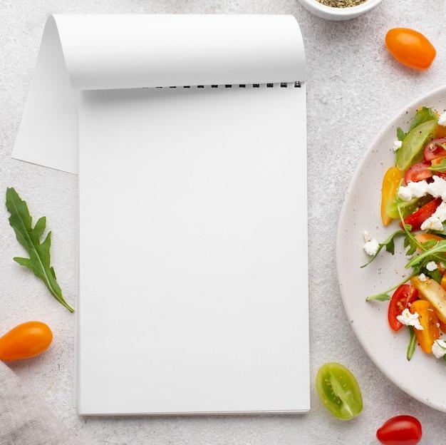 Ensalada de mezcla de tomate vista superior con queso feta y bloc de notas en blanco
