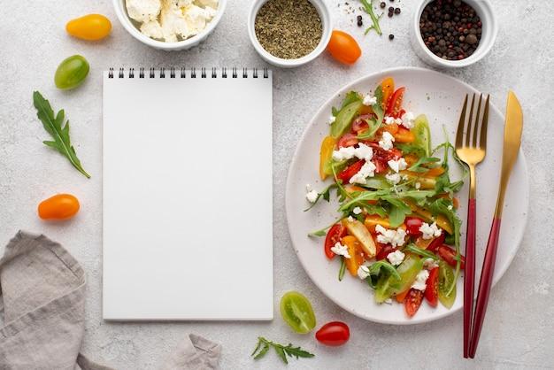 Ensalada de mezcla de tomate vista superior con queso feta, rúcula y cuaderno en blanco