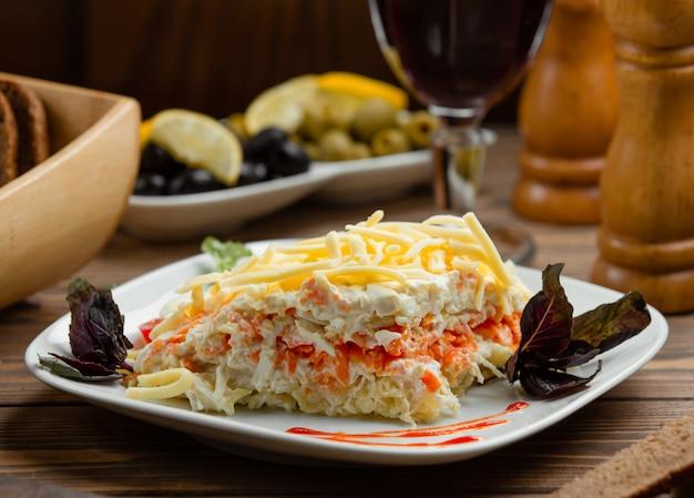 Ensalada de mimosa en porciones con clara de huevo, zanahoria al vapor, papa, queso