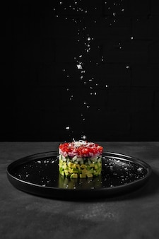 Ensalada minimalista en forma redonda y sal