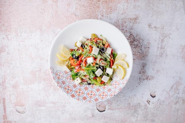 Ensalada mixta de verduras con cubitos de queso blanco y rodajas de limón.